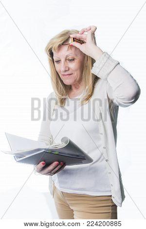 Senior blonde woman having troubles reading a magazine article, bad eyesight