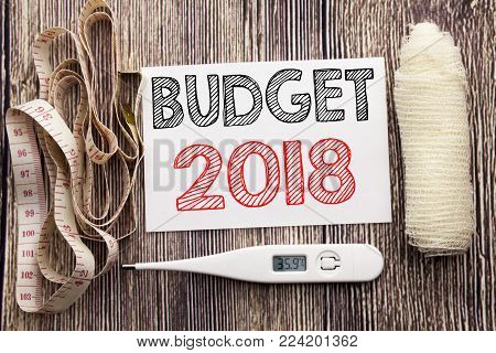 Handwritten text showing Budget 2018. Business fitness health concept writing for Household budgeting accounting planning written on wood wooden background with bandage and thermometer