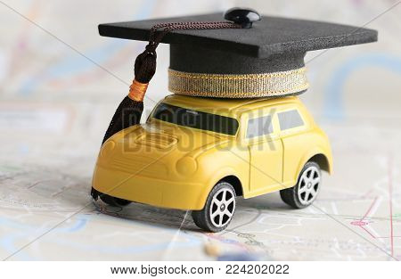 Graduate study abroad inter school concept : Graduation cap over yellow car on Bangkok city map, road to succes in life. Mortarboard Graduate learning program, Education and back to school concept