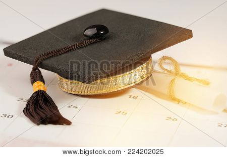 Graduate study abroad concept : Graduation cap on calendar paper near white scroll certificate show Time for Graduate study abroad program and Back to School and Studies lead to success
