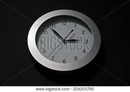 Wall clock, dial with arrows, soon three hours. Minute, hour and second hands. oval shape, shadows, hue, circle in perspective