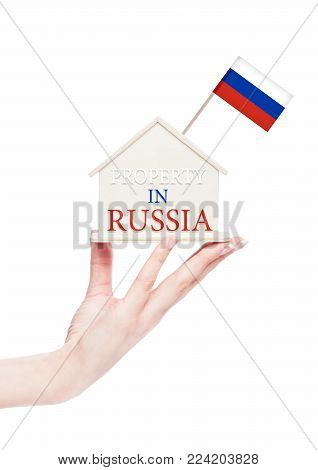 Female hand holding wooden house model with Russia flag on top. Property in Russia text