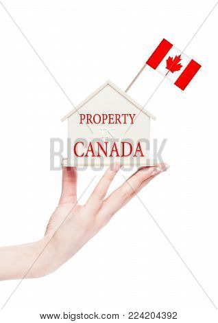 Female hand holding wooden house model with Canada flag on top. Property in Canada text
