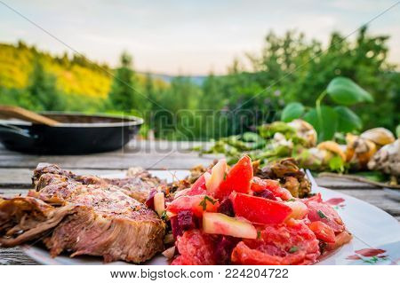 Nice Meal Of Pork Ribs And Fresh Tomatoes Eaten Outside In Summer