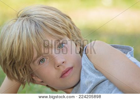 Portrait of a boy laying,resting his head on his hand poster