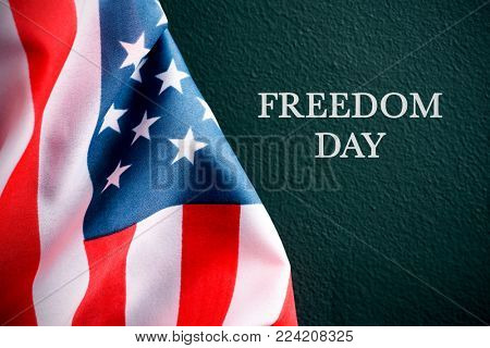 the flag of the United States and the text freedom day against a dark green background