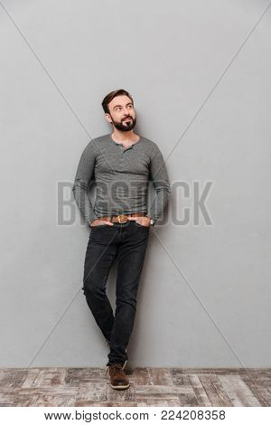 Full length portrait of a confident casual man standing and looking away over gray background