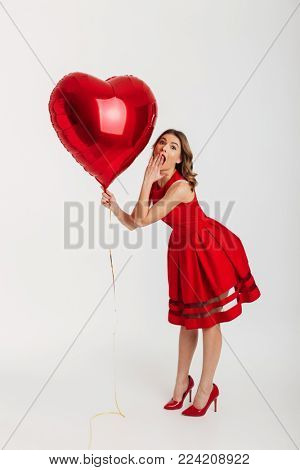 Full length portrait of a surprised young woman dressed in red dress holding air balloon while posing and celebrating isolated over white background