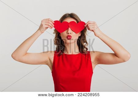Portrait of a lovely young woman dressed in red dress holding two paper hearts at her face isolated over white background