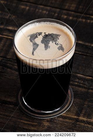 Glass of stout beer top with earth map shape on wooden background