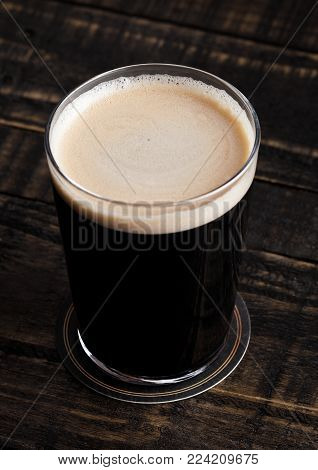 Glass of stout beer top with white foam on wooden background