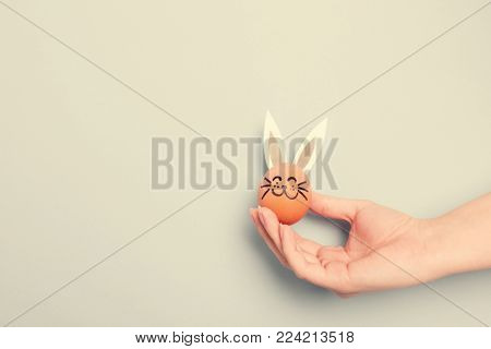 A hand holding little Easter bunny with paper ears, made from and egg. Easter symbol.
