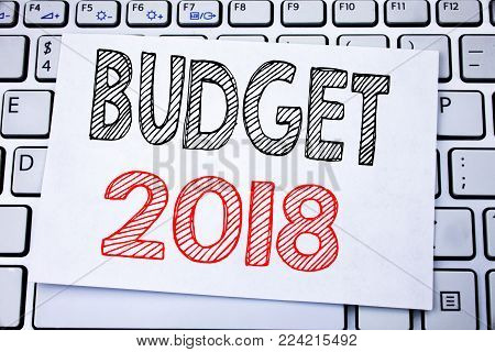 Handwritten text caption showing Budget 2018. Business concept writing for Household budgeting accounting planning written on sticky note paper on white keyboard background.