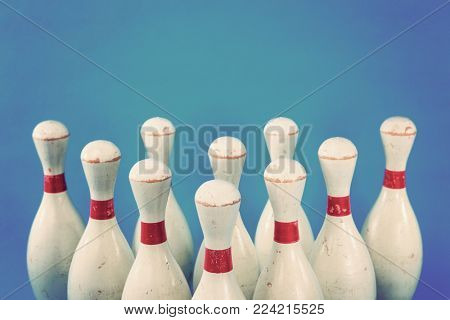 Vintage wooden bowling pins on a blue background