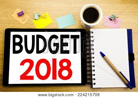 Word, writing Budget 2018. Business concept for Household budgeting accounting planning Written on tablet, wooden background with sticky note and pen