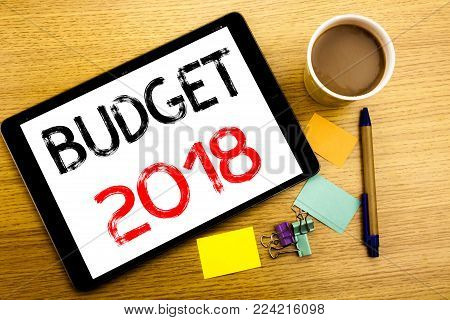 Handwritten text caption showing Budget 2018. Business concept writing for Household budgeting accounting planning Written on tablet, wooden background with sticky note and pen