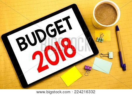 Conceptual hand writing text caption showing Budget 2018. Business concept for Household budgeting accounting planning Written on tablet, wooden background with sticky note and pen