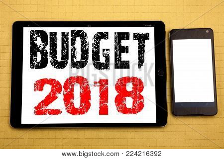 Hand writing text caption inspiration showing Budget 2018. Business concept for Household budgeting accounting planning Written on tablet, wooden background with sticky note and pen