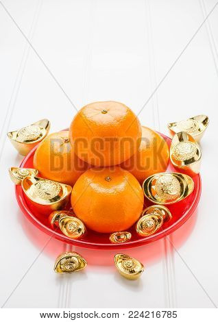 Chinese New year,gold ingots and tangerine oranges on white wood table top,Chinese Language ingot mean wealthy