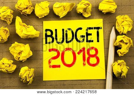 Budget 2018. Business concept for Household budgeting accounting planning written on sticky note paper on vintage background. Folded yellow papers on the background