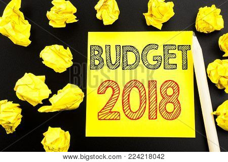 Handwritten text showing Budget 2018. Business concept writing for Household budgeting accounting planning written on sticky note paper on black background. Folded yellow papers on the background