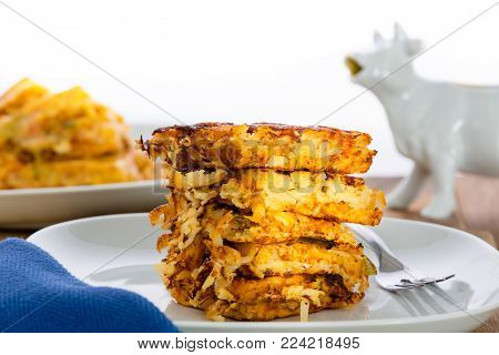 Stack of crispy waffle hash browns, or shredded potato pancakes, on a plate ready for a tasty breakfast in a low angle side view