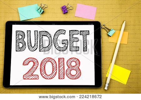 Word, writing Budget 2018. Business concept for Household budgeting accounting planning Written on tablet laptop, wooden background with sticky and pen