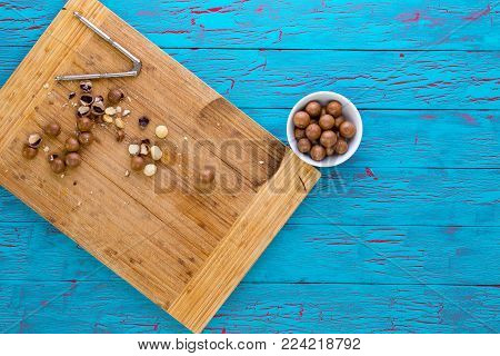 Preparing fresh macadamia nuts for eating with an overhead view of a bamboo board with cracked and shelled nuts and a nutcracker with a bowl of nuts in shells alongside on blue crackle painted wood