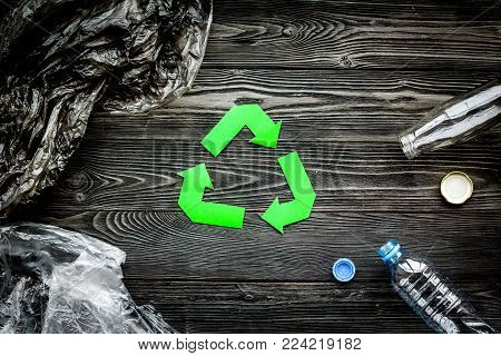 Recycle plastic and polyethylene waste. Botlles and bags near green recycle sign on grey background top view.