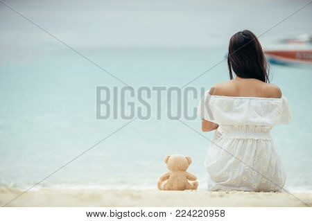 Asian girl wearing a long white dress walking or standing at the beach on vacation weekend. Single lady sitting at the beach by alone. Girl with white dress on the beach.