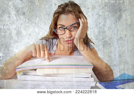 young attractive and beautiful tired student girl leaning on school books pile tired and bored after studying preparing exam looking wasted isolated in grunge studio background