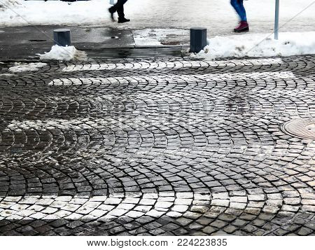 Stone pavaged pedestrian crossing in a small town at winter time.