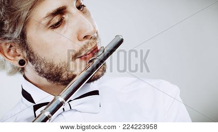 Flute music playing professional male flutist musician performer. Young elegant stylish man with instrument, close up