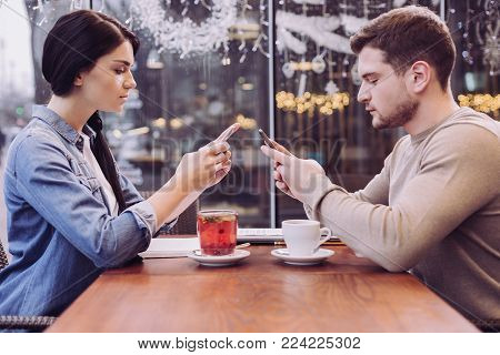 Digital trap. Attractive pensive earnest couple ignoring each other while staring at phones and sitting in front of each other