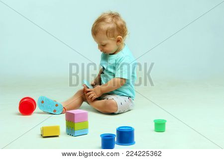 Little baby boy sitting among toys.Adorable Baby Boy Sitting and Playing Toys. Cute little Baby Boy.