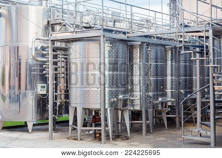 Modern technological industrial equipment of wine factory. Large stainless steel wine distilling vats.