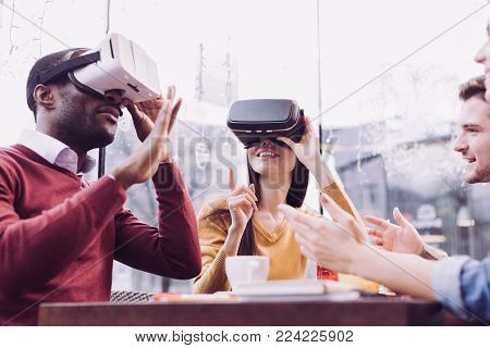 VR headset. Pleasant young two friends gesturing while experiencing VR glasses and woman smiling