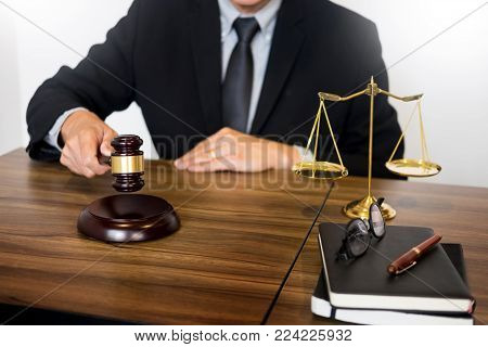 Male Judge Lawyer In A Courtroom Striking The Gavel On Sounding Block