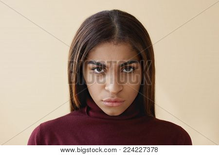 Close up studio portrait of grumpy angry young African American brunette lady pouting lips and frowning, expressing her disapproval and negative attitude while having fight with her boyfriend