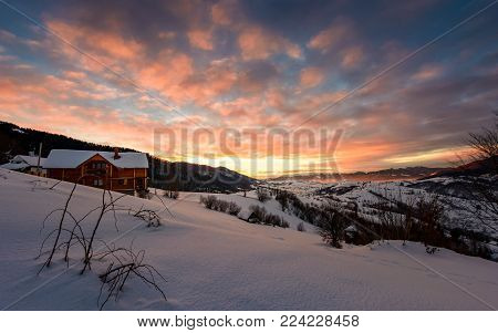 winter sunrise with red clouds in the village. beautiful winter countryside in mountains with snowy slopes
