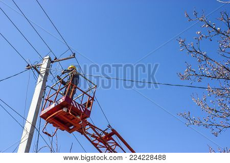 Power lines. Man on the aerial platform. Electrician connects the electrical wires. Man is an electrician.