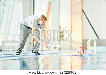 Happy trainer encouraging his young student while she swimming in pool
