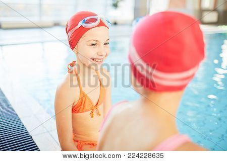 Happy girl in swimsuit, swim-cap and goggles looking at her friend while talking to her by swimming-pool