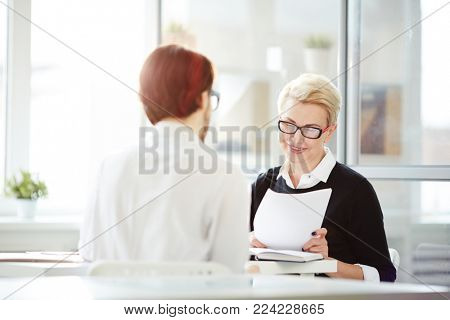 Successful employer with resume of young applicant asking him questions during interview