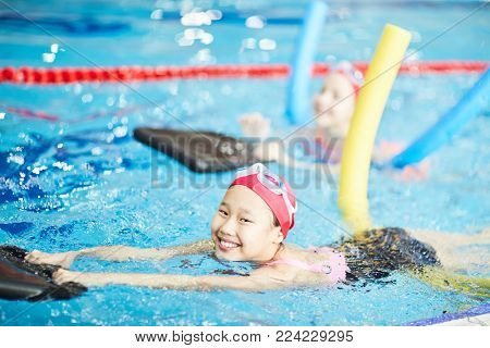 Cute girl having fun while learning to swim with special resistance inflatable equipment