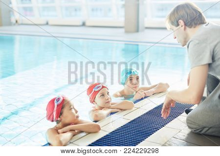 Three schoolkids in swimwear listening to their trainer during lesson of swimming
