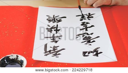 Writing Chinese calligraphy with phrase meaning wish you good fortune and may all your wishes come true