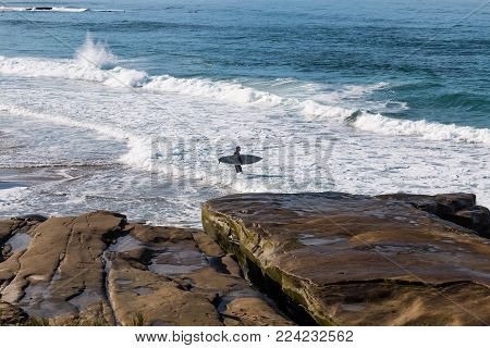 LA JOLLA, CALIFORNIA - JANUARY 27, 2018:  A surfer headed out to sea at Windansea Beach, a popular beach with a reputation as a surfbreak, and the home break of many notable surfers in Southern California.