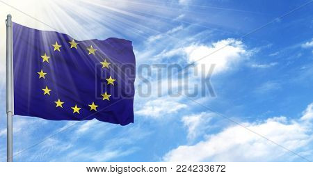 Flag of European Union on flagpole against the blue sky.
