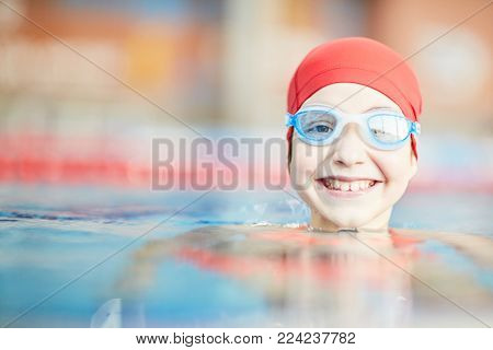 Happy young swimmer in goggles and swim-cap looking out of water of swimming-pool